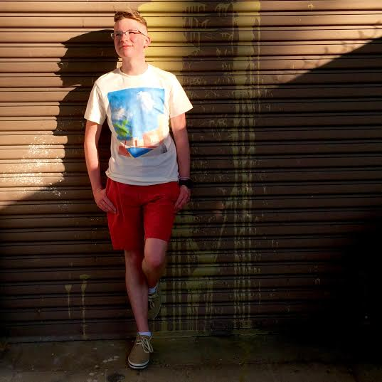 Casey Hoke leans against a brown metal wall with his left leg propped up against it. His hands are in the pockets of his red shorts and he smiles looking slightly to his right. The sun lights up the upper half of the photo on a diagonal slant.