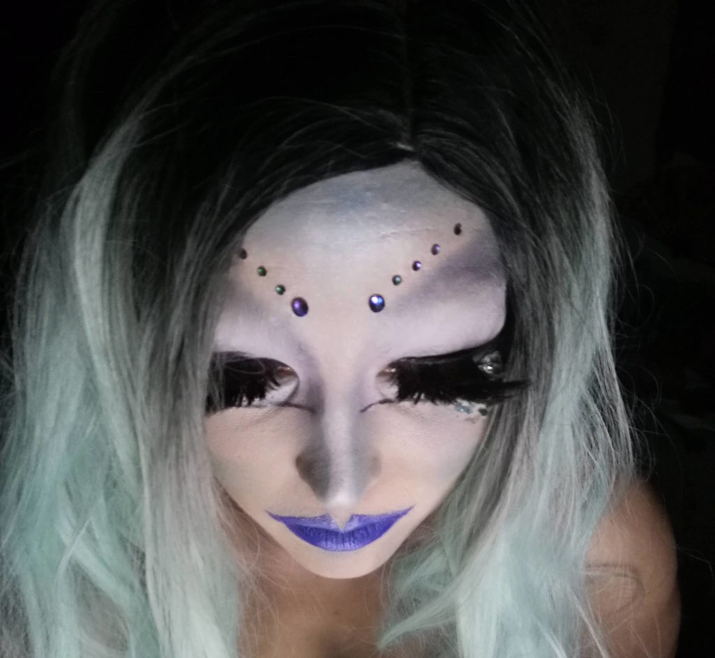 Burnina looks down and the photo is taken from above. Her drag make up is white with blue accents and her eyebrows angle upwards and are made of rhinestones. Her with is black fading to light icy blue.