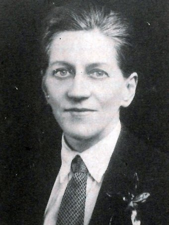 Monte Punshon, facing slightly left, wears suit and tie with slick hair and a soft smile in this black and white photograph.