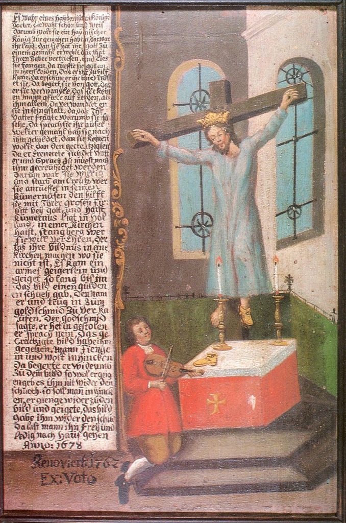 Saint Wilgefortis shown on the cross with a beard, a crown, and a light blue dress with a fiddler at her feet. There is a column of text to the left of the image.