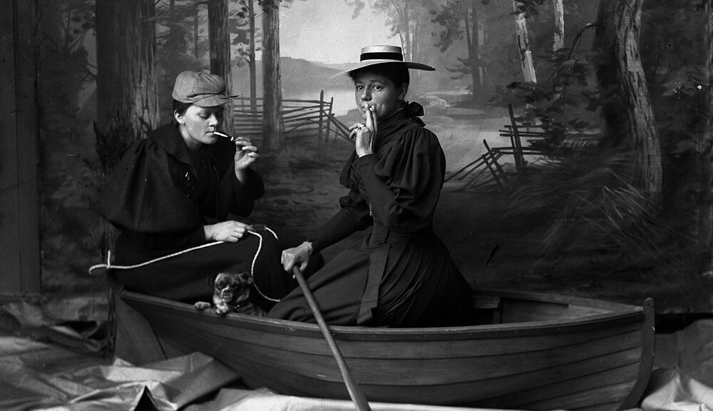 Two women sit together in a wooden row boat with a small dog in a studio with a backdrop of a misty forest. They are smoking and the woman on the right looks out towards the camera. The photograph is black and white.