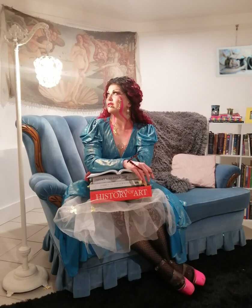 A photo of a Burnina Sparks on a blue vintage couch with a stack of art history books on her lap. She wears a shiny blue gown and has pink pleasers. She looks up toward a lap on the left.