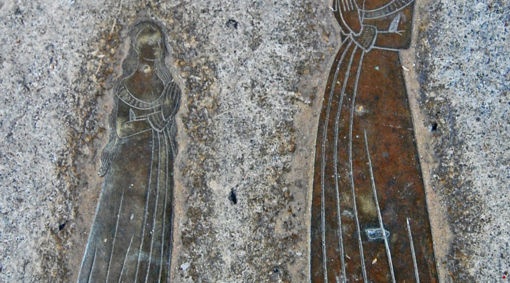 A memorial brass of two women standing side by side looking into each other's eyes. It is mounted on a grey stone wall. The woman on the left is smaller with her hair down. The woman on the right taller with her hair up. Both wear long gowns that brush the ground. The inscription is underneath the figures.